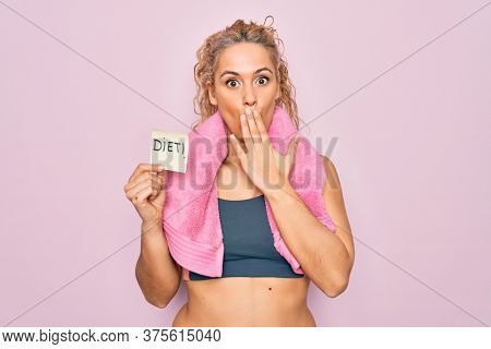 Beautiful blonde sporty woman doing sport wearing towel holding reminder with diet message covering mouth with hand, shocked and afraid for mistake. Surprised expression