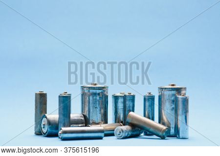 Many Used Aa Batteries On A Blue Background.