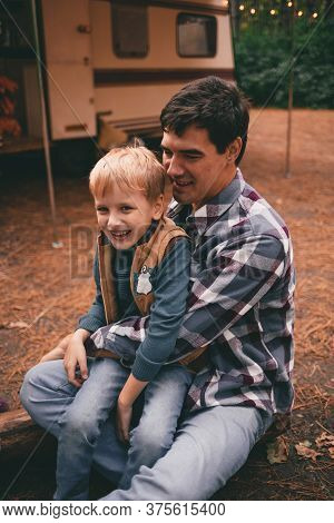 Father And Son On A Camping Trip Relaxing In The Autumn Forest. Camper Trailer. Fall Season Outdoors