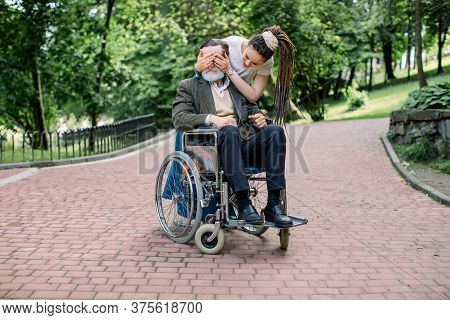 Handsome Bearded Senior Man In Wheelchair Walking In A Park. Young Pretty Granddughter Or Care Giver