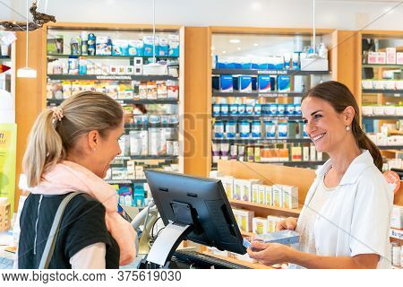 Female Pharmacist Advises Young Woman Customer At The Counter Of A Pharmacy