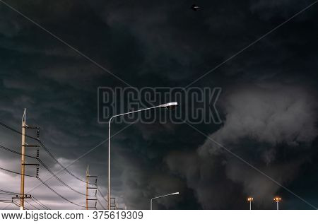 Stormy Sky With Street Light Pole And Three-phase Electric Pylons. Stormy Sky And Dark Clouds. Spotl