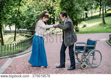 Senior Bearded Man In A Wheelchair Is Walking In The Park With His Creative Hipster Social Worker, T