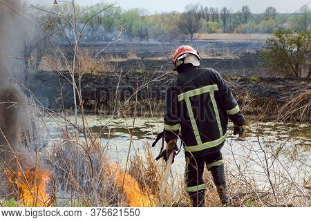 Fireman Or Firefighter Backburning And Extinguishing A Wildfire Grass And Bushfire. Closeup Of Volut