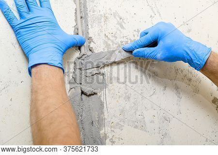 Hidden Installation Of Electrical Wires For Sockets To A Concrete Wall. The Master Is Plastering The
