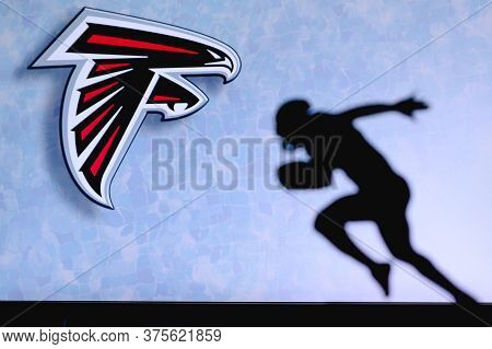 Atlanta Falcons. Silhouette Of Professional American Football Player. Logo Of Nfl Club In Background