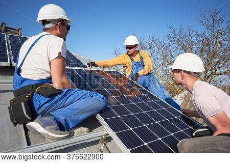Male Team Workers Installing Stand-alone Solar Photovoltaic Panel System. Electricians Mounting Blue