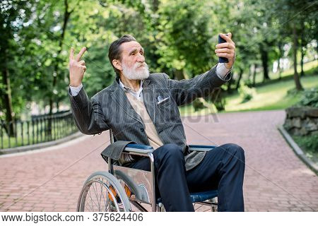 Happy Senior Disabled Or Handicapped Bearded Man Sitting On A Wheelchair In Park, Using His Smartpho