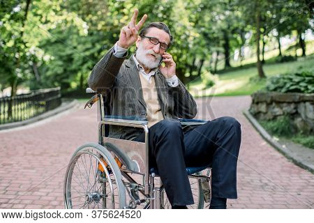 Happy Laughing Senior Handicapped Man In A Wheelchair, Walking In A Park, Using His Phone, Talking W
