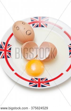 Anthropomorphic brown egg with egg shells and yoke in plate