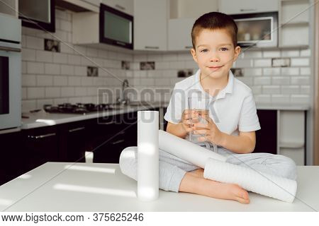 A Little Boy In The Kitchen Drinks Clean Water From A Glass, Clean Water Is A Pledge Of Health. Wate