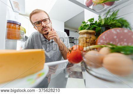Man Looking Inside Fridge Full Of Food.
