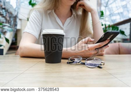 Cropped Photo Of Cheerful Young Caucasian Blond Business Woman In A White Shirt Smiling And Typing O