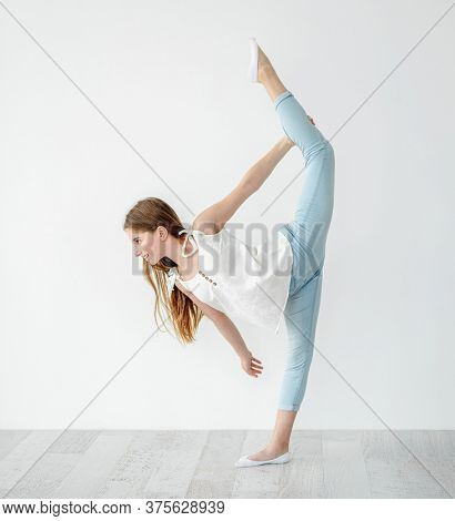 Smiling teenage girl performing vertical twine on white wall background