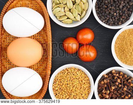 Raw Chicken Eggs, Black Pepper, Masala Powder, Allspice, Fenugreek, Green Cardamom, Tomato On Black