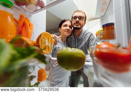 Look In The Fridge. Young And Successful Couple In Love Looks In The Fridge And Take Out Of The Frid