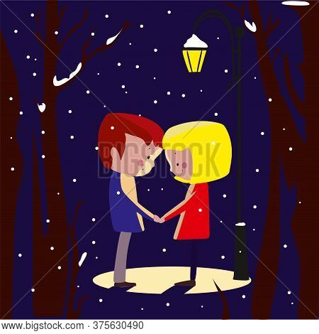 A Couple In Love Hold Hands Under A Streetlight In Winter.a Boy And A Girl In Winter Under A Street