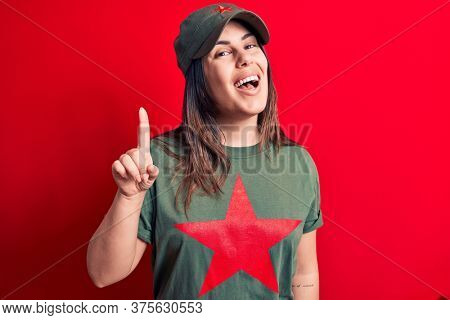 Young beautiful brunette woman wearing cap and t-shirt with red star communist symbol smiling with an idea or question pointing finger up with happy face, number one