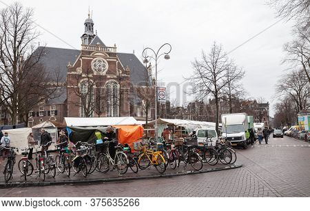 Amsterdam, Netherlands - February 25, 2017: Marketplace Noordermarkt View With Parked Bicycles And W