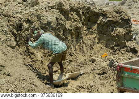 Howrah, West Bengal, India - 7th May 2017 : Indian Male Worker Digging Soil At Buliding Construction