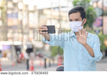 Young Man In A Medical Mask To Avoid The Spread Of Coronavirus Using Vdo Call Smartphone In The City