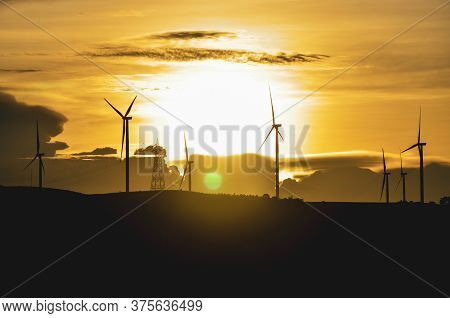Silhouette Of Wind Turbines Produce Electricity With Sunlight During Sunset Background.