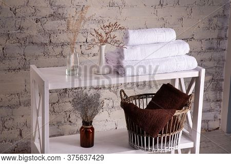 Rack With A Stack Of Three White Color Towels And Baskets With Clean Brown Towels And Toilet Decor N