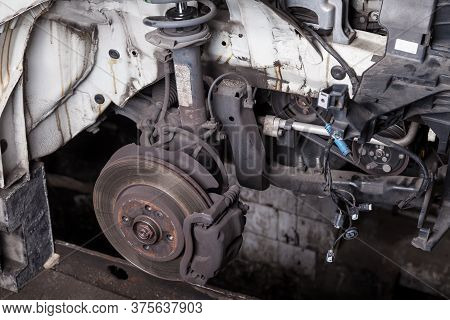 The Front Part Of The Car After An Accident In A Car Service With A Disassembled Hood And A Metal Ra