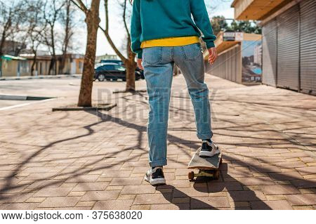Young Beautiful Caucasian Woman Rides A Skateboard.the View From The Back. In The Background, A Stre