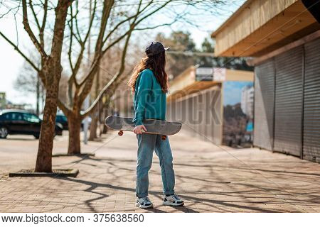 A Young Caucasian Hipster Woman Walks Down The Street With A Skateboard In Her Hands And Turns Back.