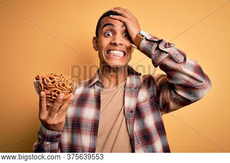 Young handsome african american man holding bowl with german baked pretzels stressed with hand on head, shocked with shame and surprise face, angry and frustrated. Fear and upset for mistake.