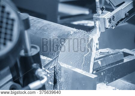 The Automatic Band Saw Machine Cutting The Metal Rod With The Liquid Coolant. The Machine Tool Opera