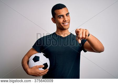 Handsome african american man playing footbal holding soccer ball over white background pointing to you and the camera with fingers, smiling positive and cheerful