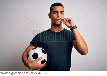 Handsome african american man playing footbal holding soccer ball over white background mouth and lips shut as zip with fingers. Secret and silent, taboo talking