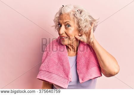 Senior grey-haired woman wearing sportswear and towel smiling with hand over ear listening and hearing to rumor or gossip. deafness concept.