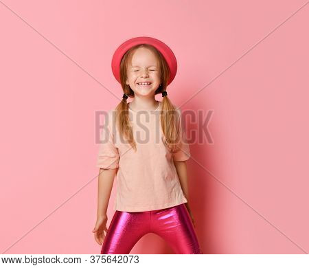 Cute Little Girl In Trendy Summer Attire And Hat Standing And Laughing While Keeping Eyes Closed. Th