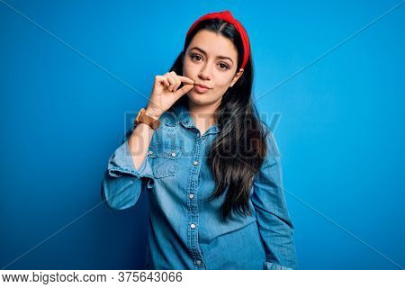 Young brunette woman wearing casual denim shirt over blue isolated background mouth and lips shut as zip with fingers. Secret and silent, taboo talking