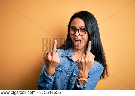 Young beautiful chinese woman wearing casual denim shirt over isolated yellow background Showing middle finger doing fuck you bad expression, provocation and rude attitude. Screaming excited