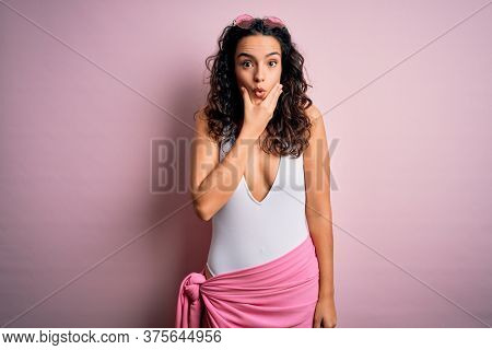 Beautiful woman with curly hair on vacation wearing white swimsuit over pink background Looking fascinated with disbelief, surprise and amazed expression with hands on chin