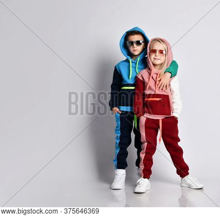 Elder Bro Hugging His Younger Sister. Stylish Sporty Kids In Colourful Tracksuits And Sunglasses. Ch