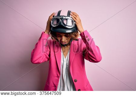 African american motorcyclist woman with curly hair wearing moto helmet over pink background suffering from headache desperate and stressed because pain and migraine. Hands on head.