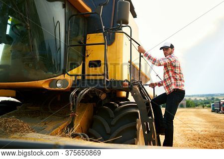 Harvester Machine Driver Climbing Into A Cab To Harvest His Wheat Field. Farmer Getting In Combine O