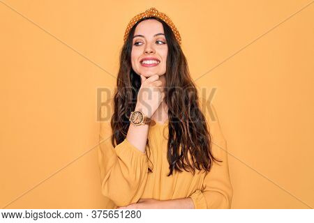 Young beautiful woman wearing casual t-shirt and diadem standing over yellow background with hand on chin thinking about question, pensive expression. Smiling with thoughtful face. Doubt concept.