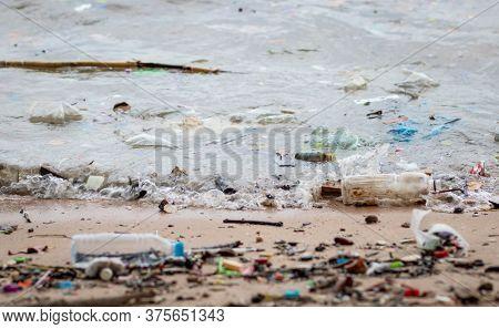 Trash On The Beach. Beach Pollution. Plastic Bottles And Other Trash On Sea Beach. Dirty Sea Sandy S