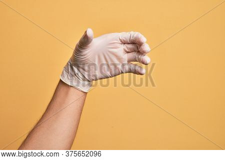 Hand of caucasian young man with medical glove over isolated yellow background holding invisible object, empty hand doing clipping and grabbing gesture