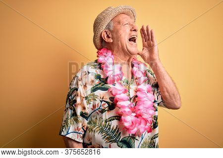 Grey haired senior man wearing summer hat and hawaiian lei over yellow background shouting and screaming loud to side with hand on mouth. Communication concept.