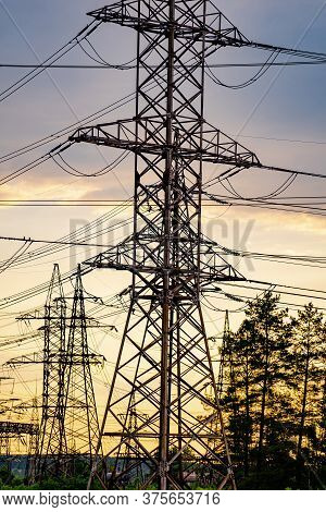 Electricity Pylons And High-voltage Power Lines On The Green Grass. Power Plant. Electrical Power Gr