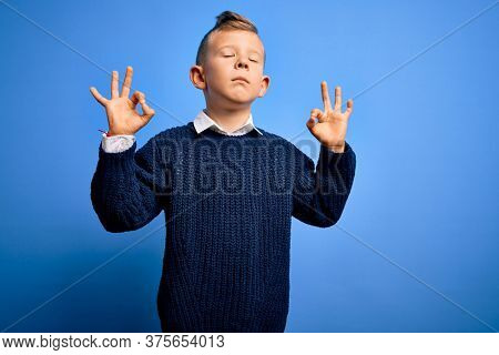 Young little caucasian kid with blue eyes wearing winter sweater over blue background relax and smiling with eyes closed doing meditation gesture with fingers. Yoga concept.