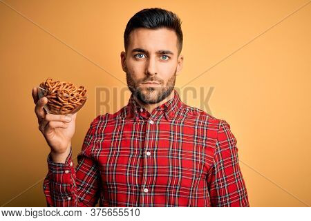 Young handsome man holding bowl with baked German pretzels over yellow background with a confident expression on smart face thinking serious