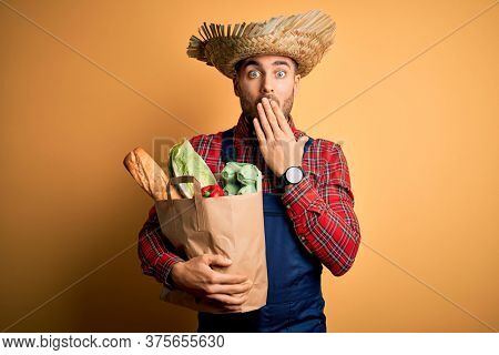 Young rural farmer man holding fresh groceries from marketplace over yellow background cover mouth with hand shocked with shame for mistake, expression of fear, scared in silence, secret concept